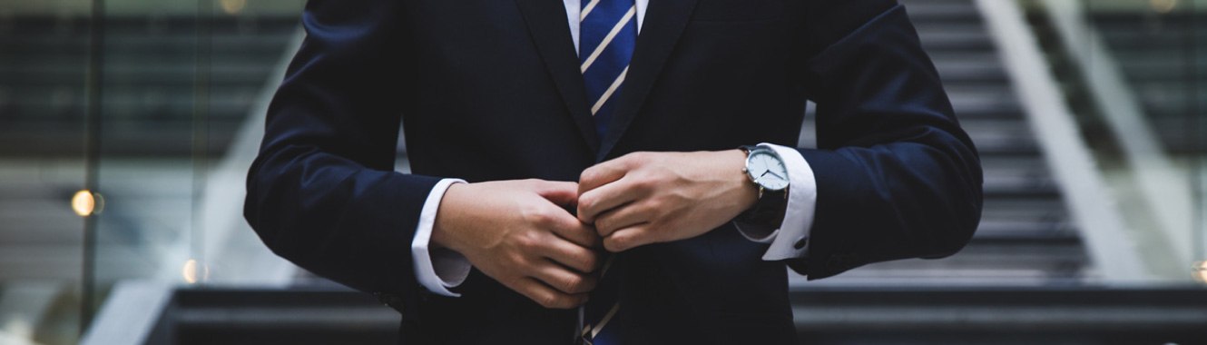 Close-up shot of a man hand's buttoning up his expensive-looking business suit. He's standing in a modern office building.