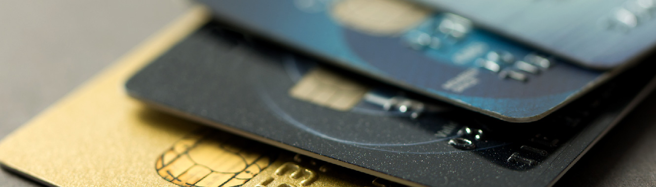 A close-up shot of four credit cards stacked on top of each other slightly fanned out.