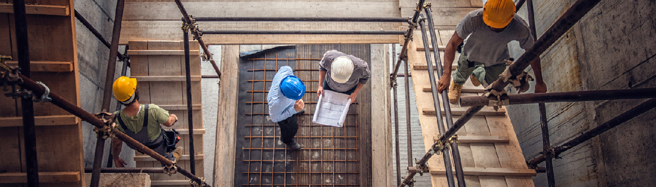 A top-down view of a construction site. Two workers talk over blueprints at the bottom of the structure.