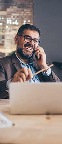 Businessman smiling while on the phone and looking at his laptop.